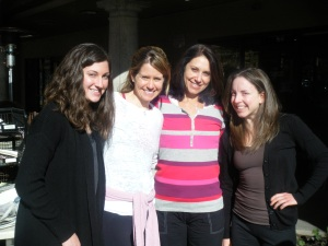 Four women standing next to each other smiling